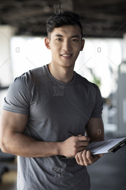 Young fitness instructor holding chart