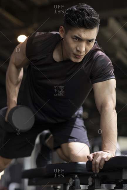 Young man working out with dumbbell at gym