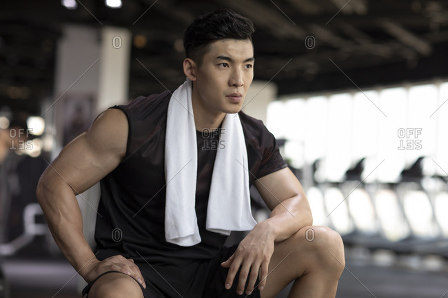 Young man taking a break from workout at gym