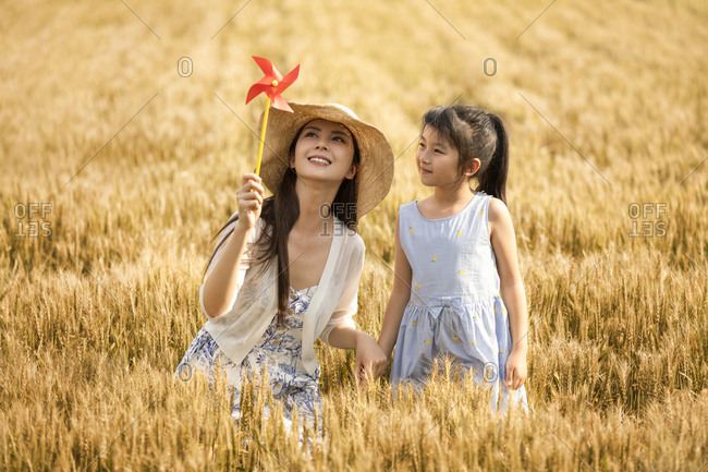 Happy mother and daughter having fun in wheat field