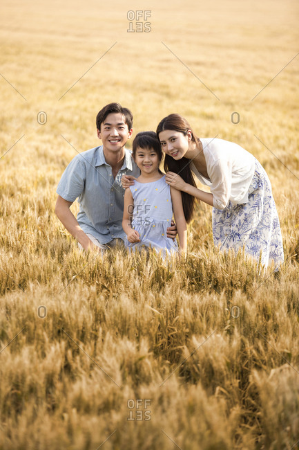 Happy young family having fun in wheat field