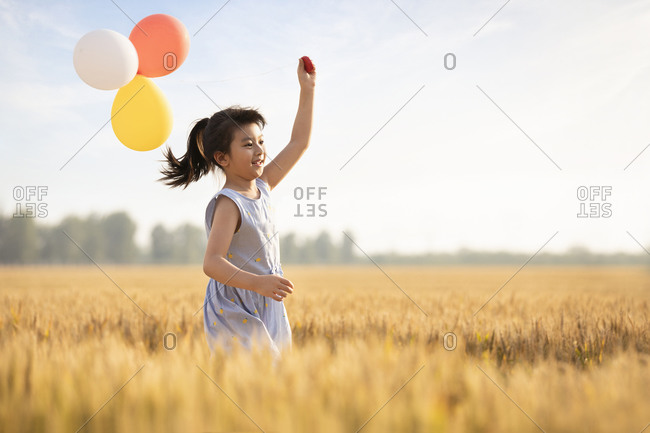 Little girl playing with balloons in wheat field