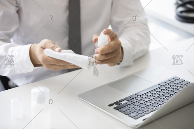 Young businessman using disinfectant in office