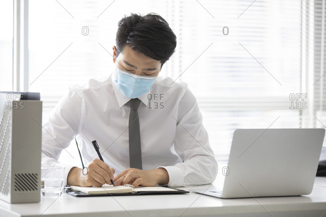 Young businessman with surgical mask working in office