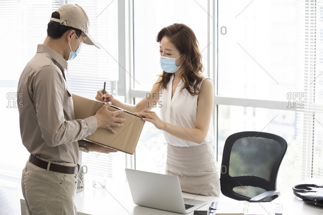 Young businesswoman signing for express delivery in office