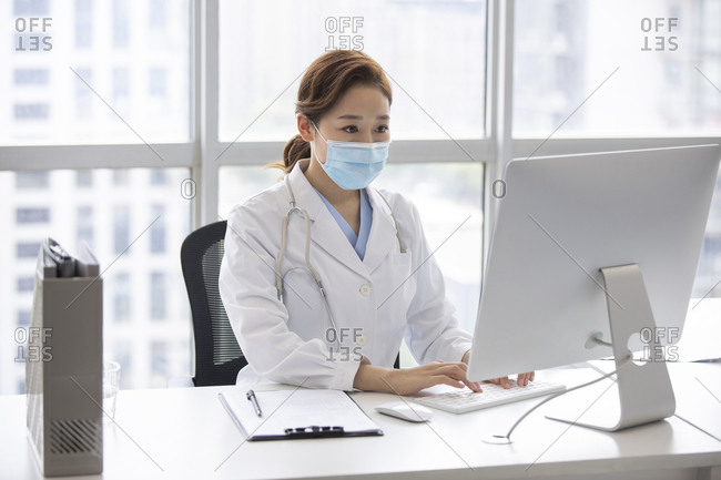 Young doctor using computer in doctor's office