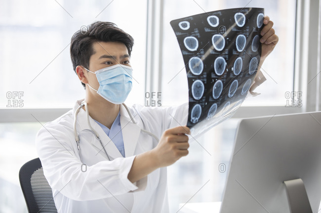 Young doctor checking X-ray image