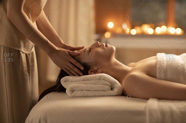 Young woman receiving facial massage at spa center