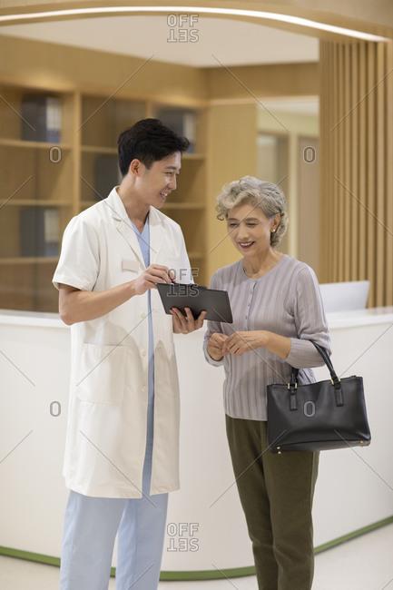 Doctor talking to senior woman in hospital corridor