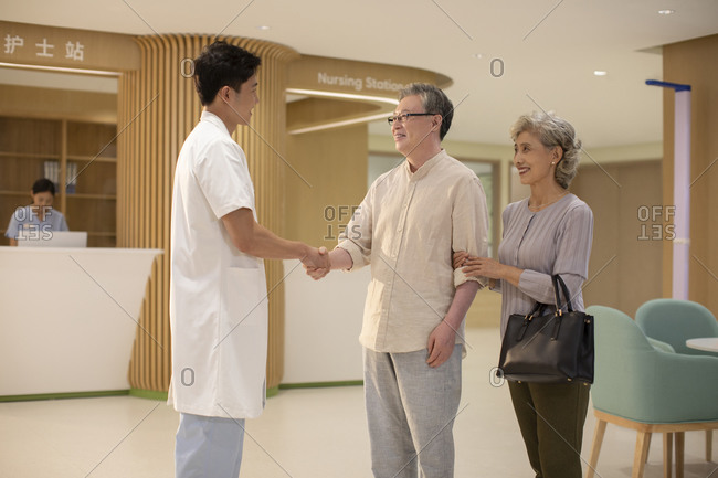 Doctor shaking hands with senior couple in hospital corridor