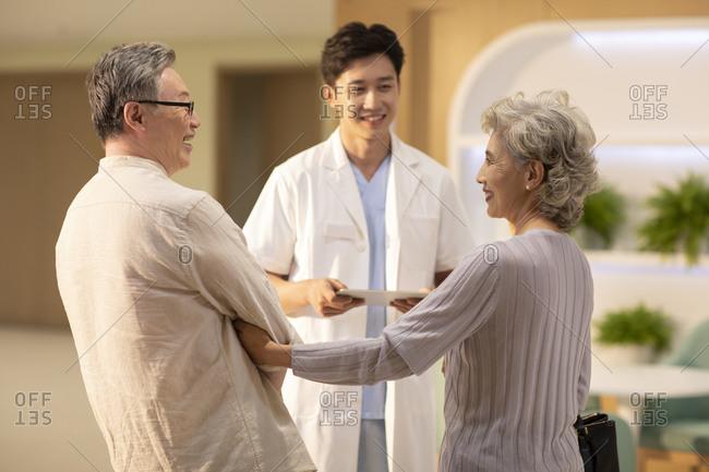 Doctor talking to senior couple in hospital corridor