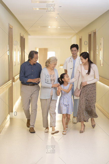 Family and doctor walking in hospital corridor
