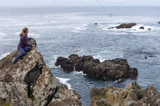 Woman admiring the rugged beauty of the British Columbia west coast along the Wild Pacific Trail in Ucluelet, Vancouver Island, British Columbia