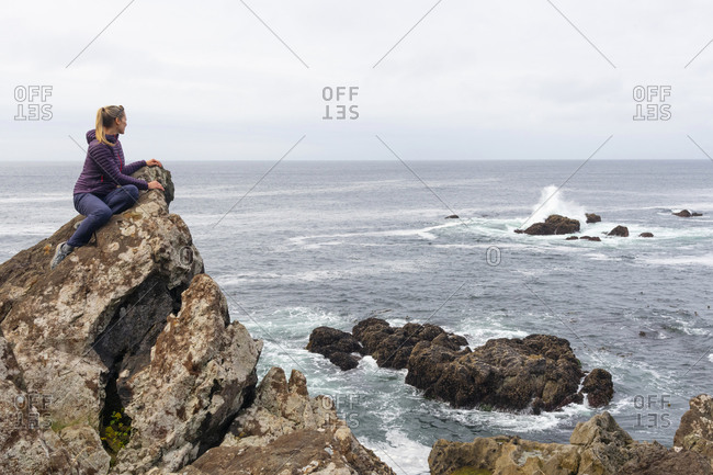 Blonde woman admiring the rugged beauty of the British Columbia west coast along the Wild Pacific Trail in Ucluelet, Vancouver Island, British Columbia