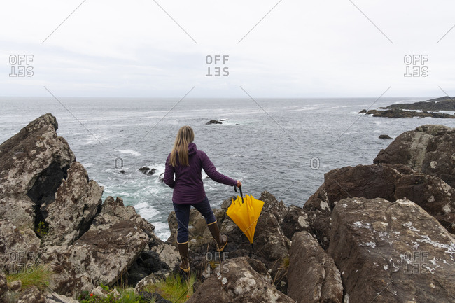 Rear view of woman with umbrella admiring the rugged beauty of the British Columbia west coast along the Wild Pacific Trail in Ucluelet, Vancouver Island, British Columbia
