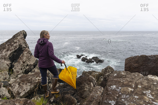 Woman standing with umbrella admiring the rugged beauty of the British Columbia west coast along the Wild Pacific Trail in Ucluelet, Vancouver Island, British Columbia