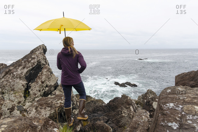 Rear view of woman with umbrella overlooking the rugged beauty of the British Columbia west coast along the Wild Pacific Trail in Ucluelet, Vancouver Island, British Columbia