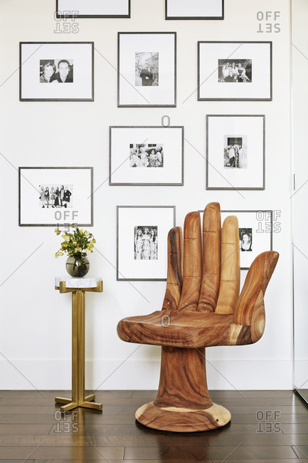 Studio City, California - January 3, 2021: Wooden hand shaped chair in front of wall of photographs in a modern condo