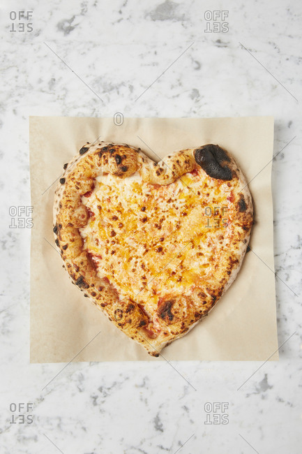 Overhead image of heart shaped pizza on parchment paper