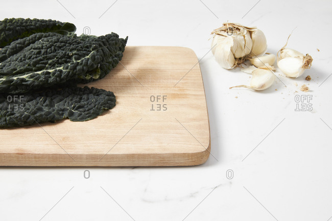 Dinasour kale on a cutting board with garlic placed on a marble countertop