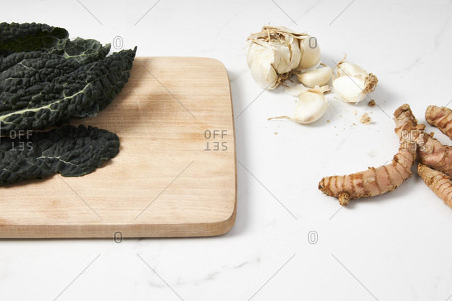 Dinasour kale on a cutting board with garlic and turmeric root placed on a marble countertop