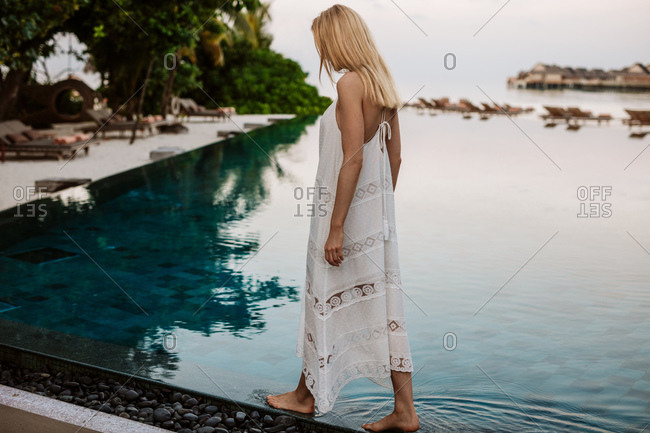 Side view of a female tourist on a luxury holiday. Woman on a holiday walking on the edge of a swimming pool.