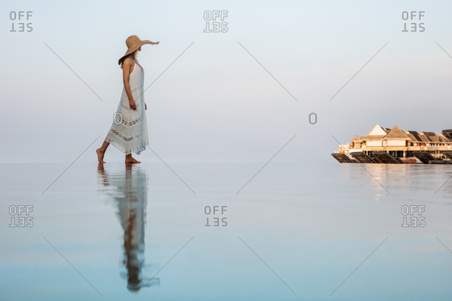 Side view of a woman in hat walking near an infinity pool with her reflection falling on water. Woman enjoying the scenic view of overwater villas at a luxury resort.