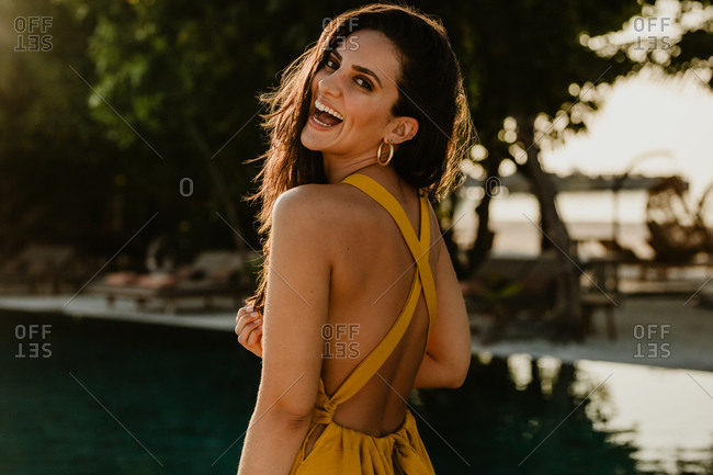 Portrait of a smiling woman standing at resort. Rear view of a woman looking back and smiling.