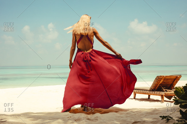 Rear view of a woman in a red flowy dress walking on the beach. Woman on a holiday at a beach walking holding a fashionable maxi dress.