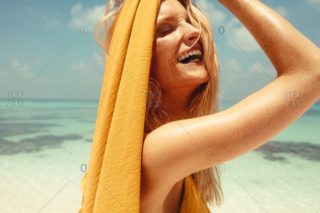 Close up of a caucasian woman laughing on the beach on a sunny day. Happy woman on beach in a joyful mood enjoying her vacation.