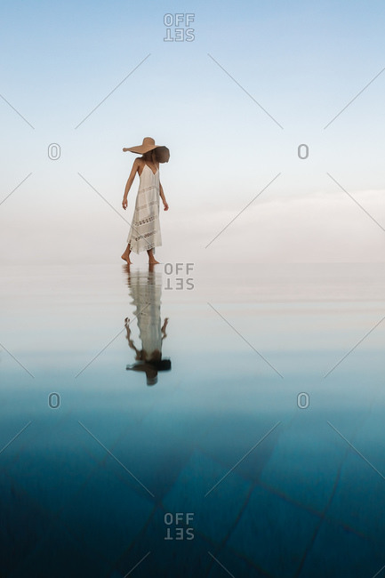 Scenic view of a woman walking at an infinity pool appearing to walk on water. Portrait of a woman walking at an infinity pool with her reflection falling on water.