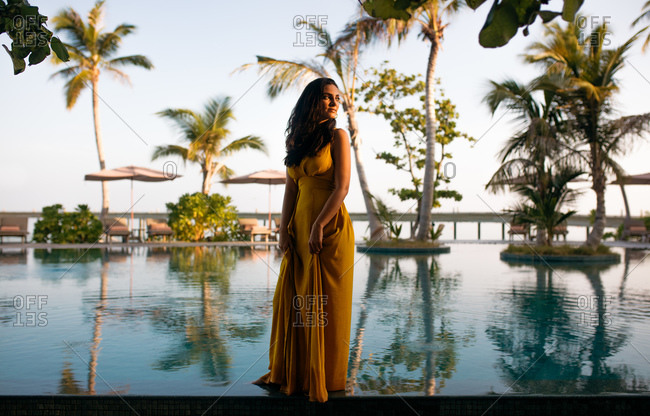 Portrait of a woman standing near a swimming pool at a luxury resort. Woman on a vacation at a tropical resort.