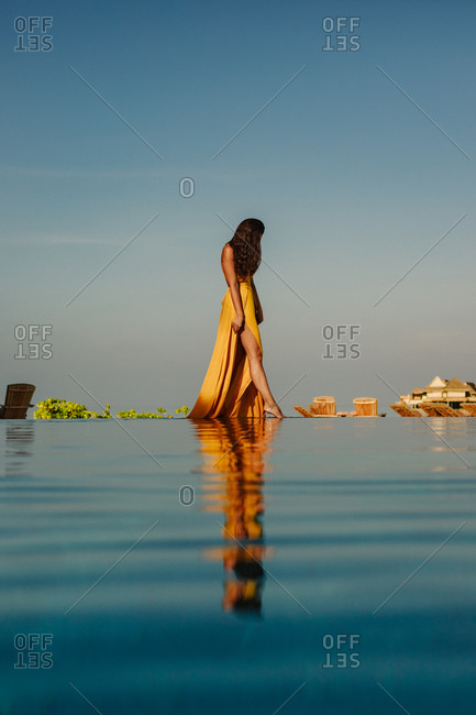 Woman in a long flowy dress touching water with her toe at an infinity pool. Portrait of a woman at a tropical beach resort on a holiday with overwater villas in the background.