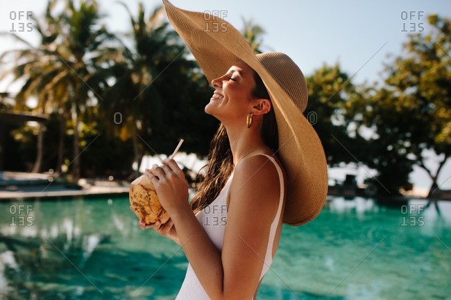 Woman enjoying tropical holiday near a swimming pool drinking coconut water. Smiling woman in big hat walking near a pool at a luxury resort.