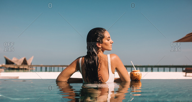 Portrait of a woman in swimsuit enjoying a swim in the pool at a luxury resort. Rear view of tourist woman relaxing in a pool enjoying coconut water.
