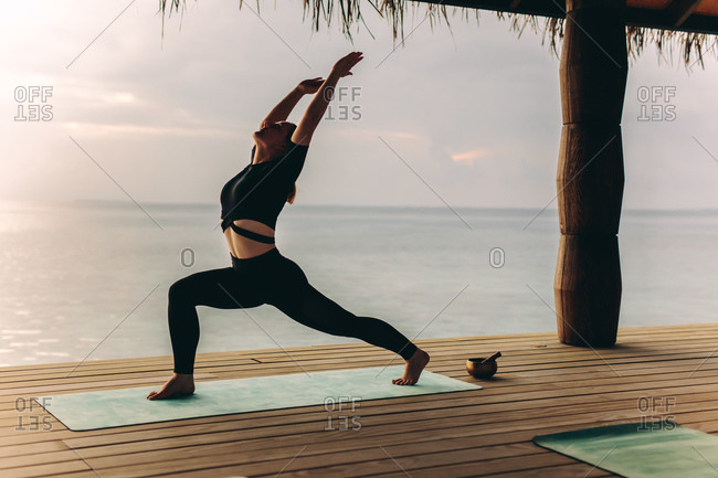 Woman standing on an overwater villa practicing yoga. Woman in warrior yoga position near the sea.