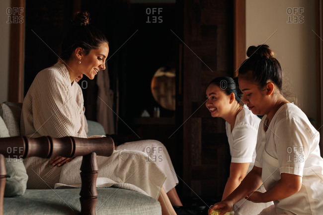 Two spa therapists providing pedicure service to a customer. Female masseuse massaging the feet of a woman.