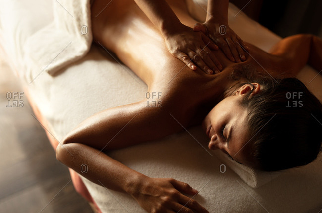 Close up of a woman getting massage therapy at a spa. Masseuse giving a back massage to a woman at a spa.