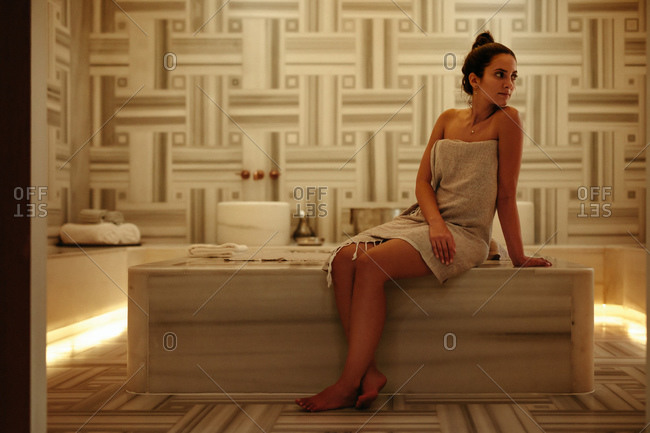 Woman with a towel wrapped around sitting in a Turkish hammam. Woman at a luxury spa for a relaxing massage therapy.