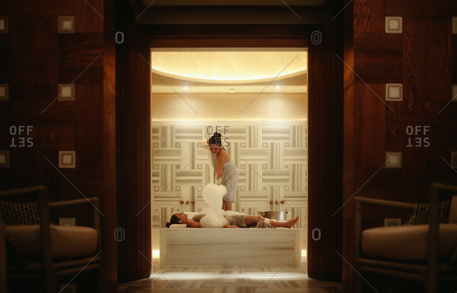 Spa attendant giving a traditional Turkish bath to a woman. Tourist woman at a luxury spa experiencing Turkish hammam.