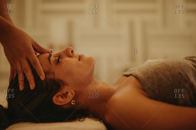 Close up of a woman lying down with eyes closed getting a forehead massage. Therapist giving a relaxing massage to a woman at a spa.