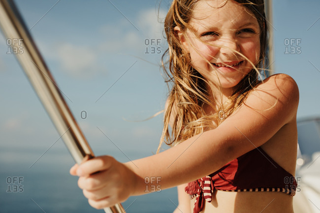 Close up a little girl on enjoying a yacht ride on a sunny day. Girl on a holiday standing on a yacht holding a rod.