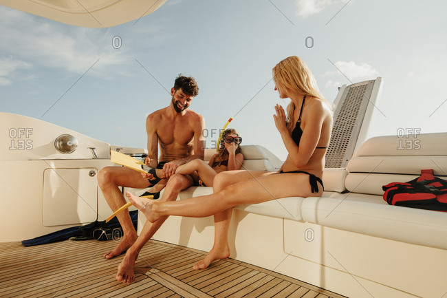 Happy family enjoying their holiday sailing on a luxury yacht. Happy family excited to go snorkeling