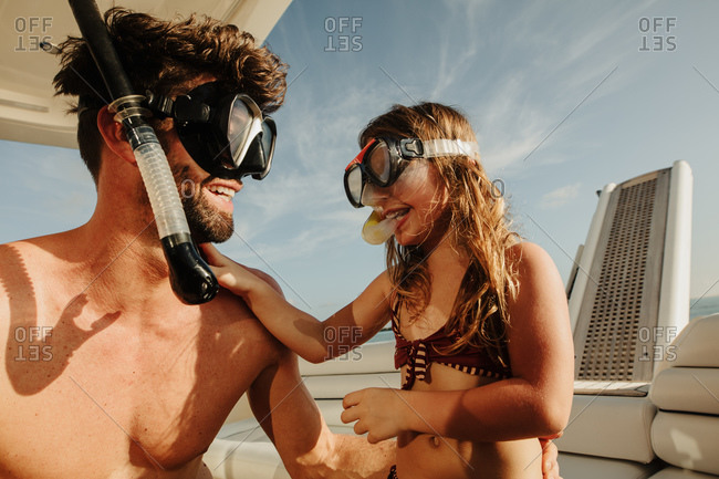 Close up of man and daughter sitting on yacht wearing diving masks. Father and daughter getting ready for underwater diving adventure on a sunny day.
