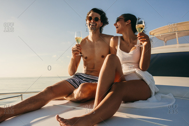 Happy couple sitting on a yacht enjoying wine. Couple on a luxury yacht ride on a sunny day.