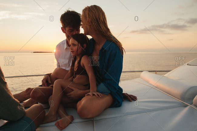 Family on a vacation enjoying the beautiful sea from a yacht. Little girl sitting on a luxury yacht with her parents at sunset.