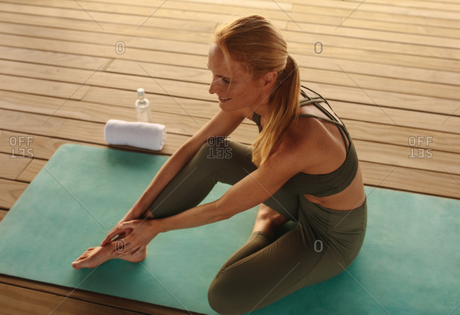 Health conscious woman doing yoga. Fitness woman sitting on exercise mat practicing yoga position holding her foot.