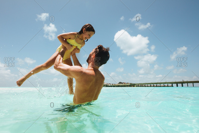 Father and daughter playing in water on the beach. Man lifting daughter standing in water at a beach resort.