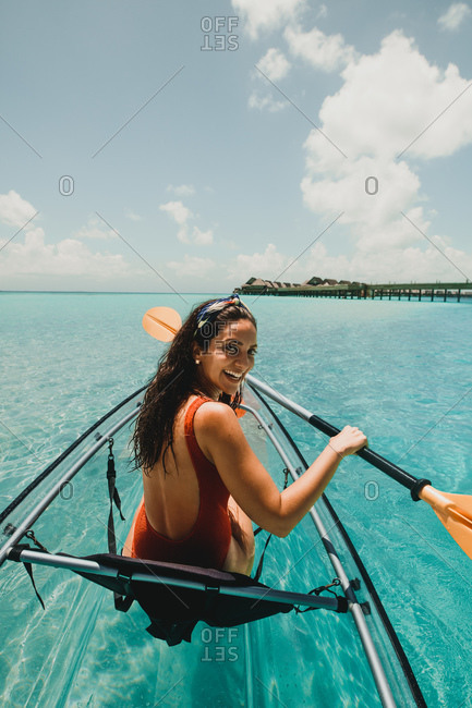 Happy woman enjoying a boat ride in the sea. Rear view of a tourist woman rowing a transparent canoe on a tropical beach resort.
