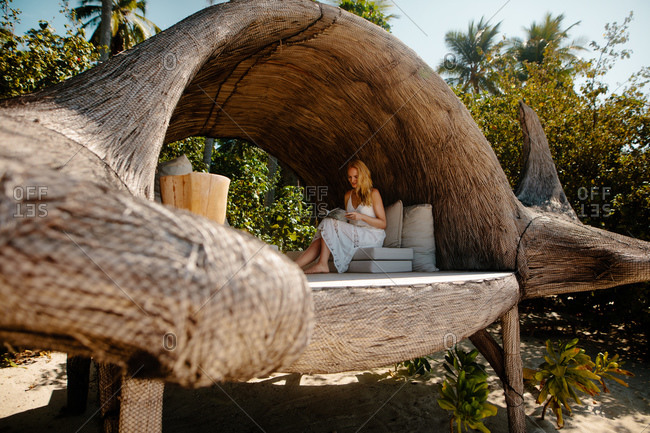 Woman sitting in a tree house reading book. Tourist woman sitting inside a manta fish shaped lounge.